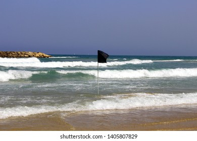 Black warning flag flapping in the wind at stormy weather.Black Flag on the sea shore-warning about dangerous current and waves. Swimming is prohibited.