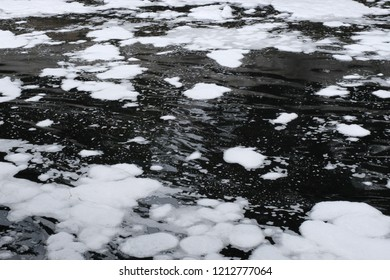 Black waste water with white foam on water surface environmental pollution of nature from effluent factory.