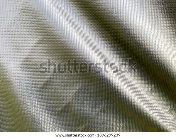 black waterproof tarp fabric hanging with natural folds with shadows