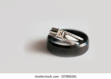 Black wedding band and square stone engagement ring stacked and isolated on white