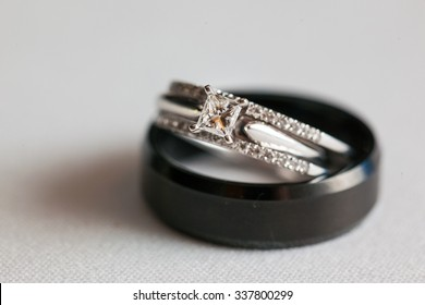 Black wedding band and square stone engagement ring stacked and isolated on white closeup
