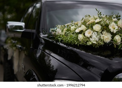 A black wedding car decorated with white roses, bridal bouquet, just married
