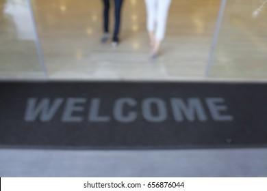 Black welcoming mat blurred.