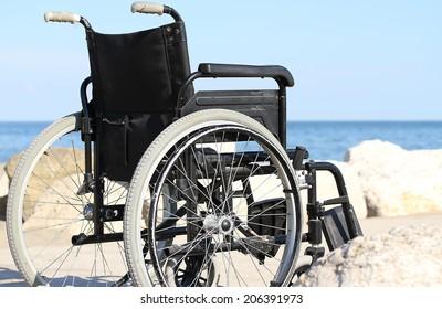 black wheelchair on the rocks near the blue sea