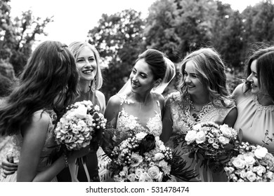 Black and whilte photo of charming bride and bridesmaids smiling to each other