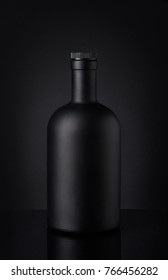 Black whiskey bottle on dark background