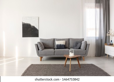 Black and white abstract painting on empty wall of cozy living room interior