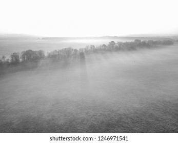 Black and white aerial view of misty field in sunrise in Bavaria