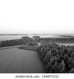 Black and white aerial view of road through misty countryside