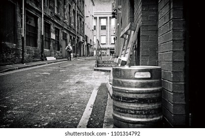 A black and white analogue image of a lonely figure walking down an old alleyway in Glasgow town center