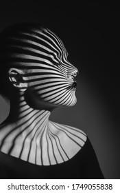 Schwarz-Weiß-Kunst-Modeporträt einer schönen Frau mit einem Lichtstrahl auf ihr Gesicht. Fashion Art Studio Portrait