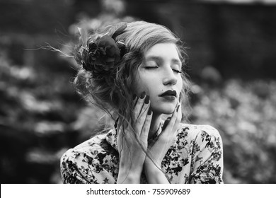 Black and white art monochrome photography. A woman with curly hair in a floral dress