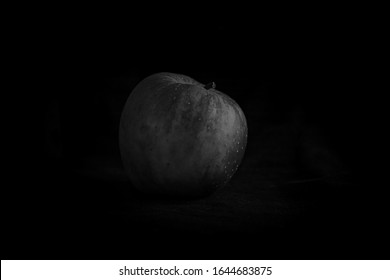 Black and white art photography of an apple on a black background. Artistic photo of fruit. Apple as a moon.