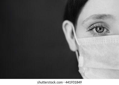 black and white art photography monochrome, red-haired girl with a medical mask on a red background, woman doctor, woman with intense look, European, half of the face, hair pinned