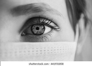black and white art photography monochrome, red-haired girl with a medical mask on a white background, woman doctor, female blue eye, macro, gauze bandage