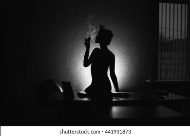 black and white art photography monochrome, photo noir, retro, silhouette of a girl in front of a window,  a woman smoking a cigarette in the mouthpiece, a woman with a pen on head sitting on a table