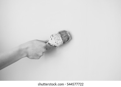 Black and white art photography monochrome, paint brush in a man's hand on a white background.
