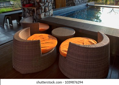 Black and White Artificial rattan chair and table beside swimming pool.