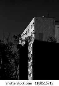 Black and white artistic photography of a sunset in a block neighbourhood casting shadow on an eastern europe flat block