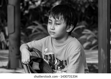 Black and White Asian boy sitting hot and sweaty at park alone holding hat