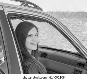 black and white attractive girl in the car in the passenger seat.