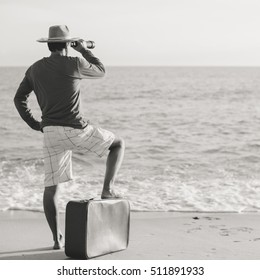Black and white back side view of traveler with suitcase watching in telescope. Male looking through a spotting scope on sunny sky outdoors background