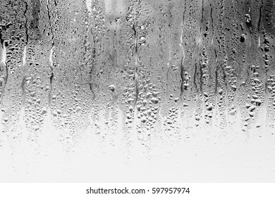 Black and white background of the condensate flowing water on the window glass