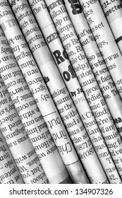 A black and white background of English language newspapers folded and stacked in a diagonal position and viewed in close up