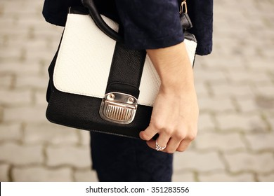 Black and white bag briefcase. Female hand on a black and white purse. Close-up. Woman on a walk. Business style, a style element, accessory.