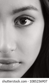 Black and white beauty portrait of ethnic asian young woman half face section looking with perfect skin. Indian features beautiful female, sight vision, natural make up cosmetics, youth lifestyle.