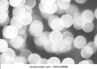 Black and white blurred picture of Christmas lights, monochromatic abstract background.