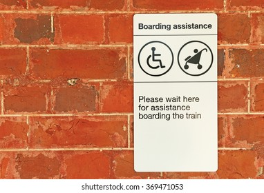 black and white Boarding Assistance sign on red brick wall