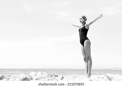 Black and white body view of a beautiful young woman swimmer diver preparing to dive off a rocky cliff by the sea, raising her arms up against a sunny blue sky. Health and beauty, sport lifestyle.