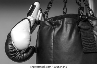Black and white of boxing glove hanging on heavy bag