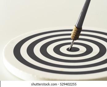Black and white bullseye dart arrow hitting target center of dartboard. Concept of success, target, goal, achievement. (selective focus)