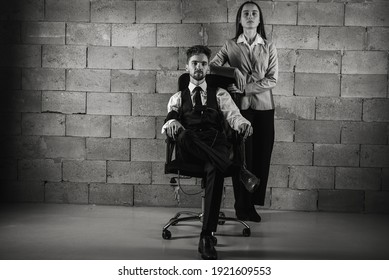 black and white. Businesspeople, business, serious young man with a beard in a dark suit and white shirt and a pretty girl, a man sitting on a dark leather office chair next to him a girl on a gray
