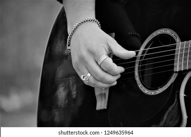 Black and white B/W photo of masculine hand with silverrings and bracelet, playing on the strings of a black guitar, close-up detail, macro, space for copy text