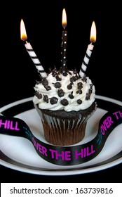 black and white candles in chocolate birthday cupcake.