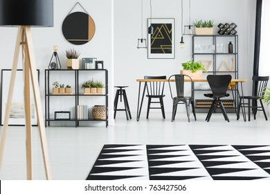 Black and white carpet in front of wooden hairpin table with black chairs and stool in white apartment interior