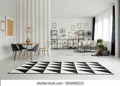 Black and white carpet in open space interior with chair at dining table and gallery of posters