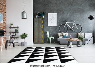 Black and white carpet in spacious living room with workspace and white bike above grey sofa