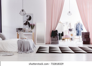 Black and white carpet in woman's bedroom interior with walk-in closet next to dressing table