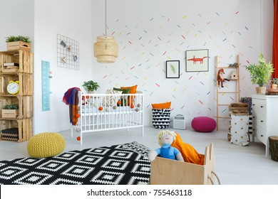 Black and white carpet and yellow pouf in scandinavian style baby's room with colorful wallpaper
