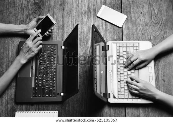 schwarz-weißer Chat auf dem Handy und Arbeit mit Notebook