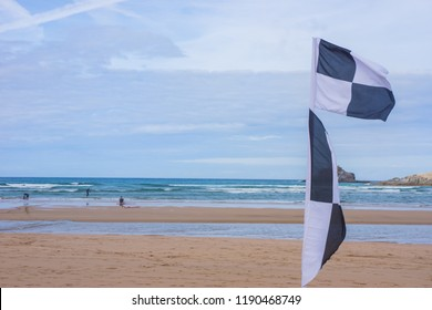 A Black and White chequered flag, indicating the safe area of the beach patrolled by lifeguards for surfers and swimmers to use.