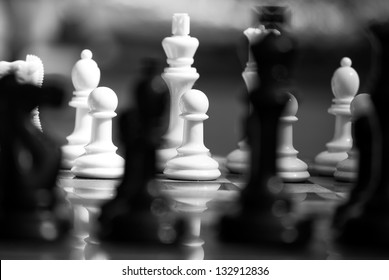 Black and white chess pieces with shallow depth of field. Abstract image.