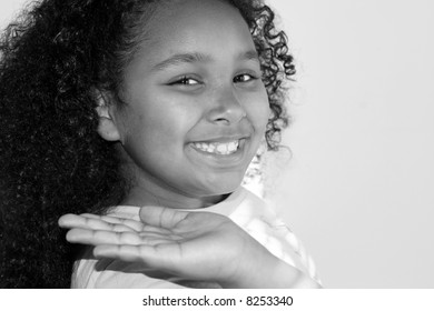 Black and white of child holding hand up with big smile.
