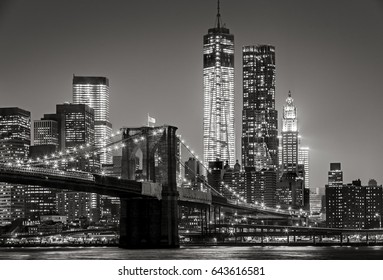 Black & White cityscape by night. View of Brooklyn Bridge and the Financial District. New York City skyline with Manhattan skyscrapers lit up at night