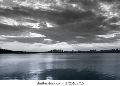 Black and white cityscape with dramatic clouds and river. Low angle image. Reflections in water. Monochromatic picture. Horizon