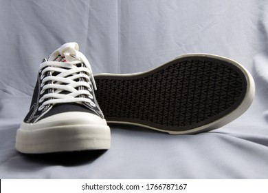 Black and white classic style canvas sneaker, shoot on a grey fabric as background